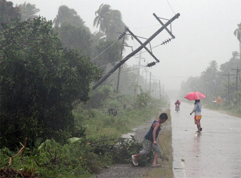 Residents brave heavy rains next to a tilted electric post after Typhoon Bophal hit the city of Tagum, Davao del Norter province, in southern island of MindanaoẢnh: AFP