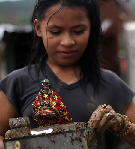 A girl cleans a religious statue of mud after landslides hit their home due to heavy rains brought about by Typhoon Bopha in Compostela town, Compostela Valley province
