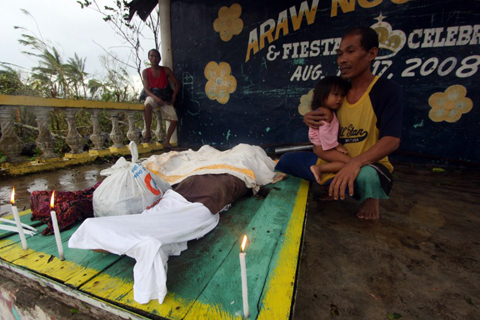 A man looks at the dead bodies of relatives killed by landslides due to heavy rains brought about by Typhoon Bopha in Compostela town