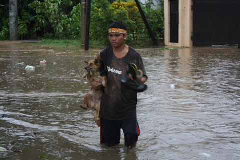 A resident carrying his pet dog wades through a flooded street due to heavy rains brought about by Typhoon Bophal in Cagayan de Oro City,