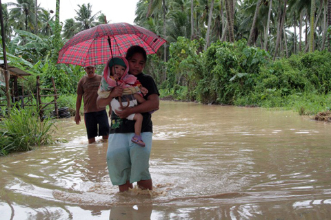 A woman carrying her child wades through a flooded road brought about by heavy rains due to Typhoon Bopha, as she evacuates to a safer place, in Pantukan town, Compostela Valley province, in southern island of Mindanao