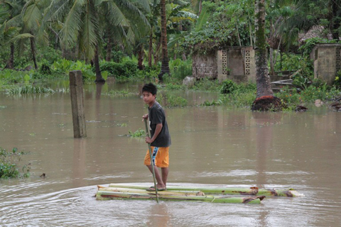 boy rides on a makeshift raft made from banana tree as he makes his way through their flooded home after heavy rans and strong winds brought about by Typhoon Bophal hit Pantukan town, Compostela Valley province