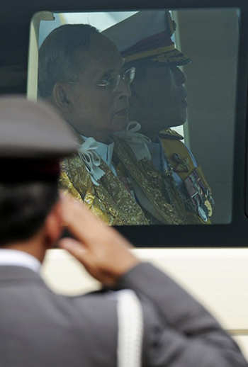 Thai King Bhumibol Adulyadej (C) sits in his royal limousine along with his son and Crown Prince Maha Vajiralongkorn (R) as he leaves the Anantasamakom Throne Hall after he delivered an address from a balcony in front of the Royal Plaza in Bangkok's historic district on December 5, 2012.