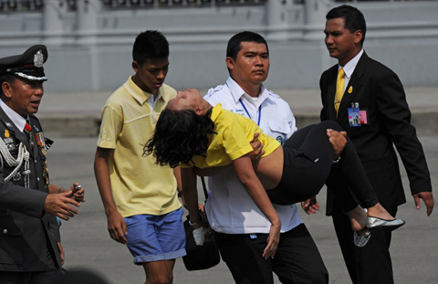 A woman is evacuated after she fainted while waiting for an address by Thai King Bhumibol Adulyadej at the Anantasamakom Throne Hall in Royal Plaza in Bangkok's historic district on December 5, 2012