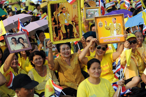People hold up portraits of Thai King Bhumibol Adulyadej as they wait for his address at the Anantasamakom Throne Hall in Royal Plaza in Bangkok's historic district on December 5, 2012. Tens of thousands of Thais crowded central Bangkok on December 5 for a rare address by King Bhumibol Adulyadej, the world's longest reigning monarch, as part of celebrations for his 85th birthday