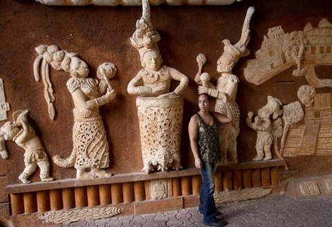 A tourist stands next to a representation of a Mayan mural at a tourist area in Playa del Carmen