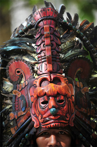 A member of a folklore group places a Mayan mask on his head in the Tikal archaeological site in Peten departament 560 km north of Guatemala city on December 20, 2012