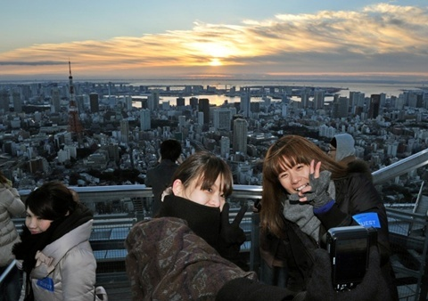 People take pictures of the sunrise on New Year's Day at the open-air Sky Deck of Roppongi Hills, some 238 metres (780 ft.) above ground level in Tokyo on January 1, 2013.