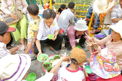 Một đại gia đình ngồi tràn ra cả lối đi để dùng bữa trưa. Chung quanh đó, nhiều du khách khác cũng tranh thủ ngồi nghỉ mệt sau một hồi chen chúc đẫm mồ hôi, mắt mũi cay xè vì khói.