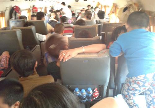 Nhiều hành khách phải ngồi ghế sút chắn cả lối đi trên tàu, xe. Ảnh: L