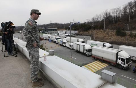 Một lính Mỹ tại cơ quan hải quan, nhập cảnh và kiểm dịch theo dõi đoàn xe trở về từ khu công nghiệp Kaesong, gần khu vực phi quân sự ở Paju, Hàn Quốc hôm 28/3. Ảnh: AP