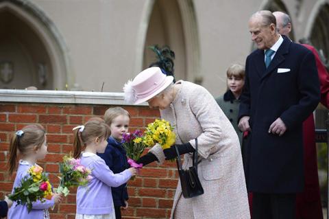 Hoàng thân Philip và Nữ hoàng Anh Elizabeth II nhận hoa từ các em bé sau khi rời khỏi một buổi cầu nguyện nhân lễ Phục sinh ở thành phố Windsor. Ảnh:AFP