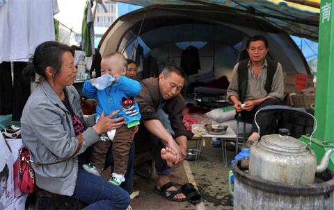 Members of a family chat outside a tent at a temporary settlement for quake-affected people in Lushan Middle School in Lushan County, southwest China's Sichuan Province, April 26, 2013. A 7.0-magnitude jolted Lushan County on April 20. (Xinhua/Li Wen)