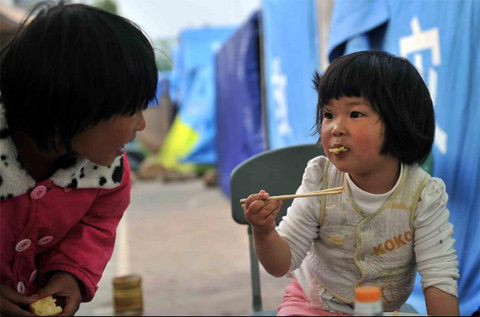 A little girl eats breakfast at a temporary settlement for quake-affected people in Lushan Middle School in Lushan County, southwest China's Sichuan Province, April 26, 2013. A 7.0-magnitude jolted Lushan County on April 20. (Xinhua/Li Wen)