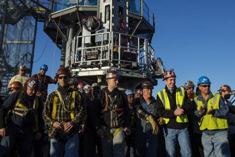 Iron workers applaud after taking a group photograph on the top of the One World Trade Center before the final piece of the buildings spire is attached in New York May 10, 2013.