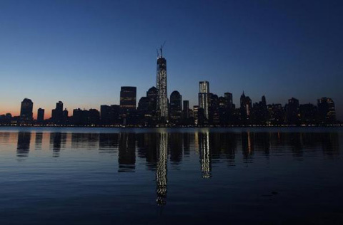 One World Trade Center in New York is reflected in the Hudson River as seen from Jersey City, New Jersey, May 10, 2013. The final piece of the building's spire will be attached later this morning.