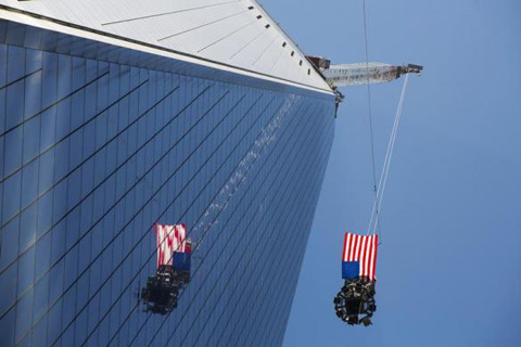 A U.S. flag flutters in the wind as the final piece of a spire is lifted to the top of One World Trade Center in New York, May 2, 2013.