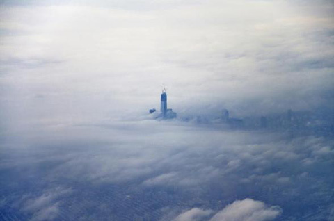 The new World Trade Center building pokes its head above the clouds over New York December 2, 2012 in this aerial photo taken by photographer Eric Reichbaum from an airplane leaving Laguardia Airport.
