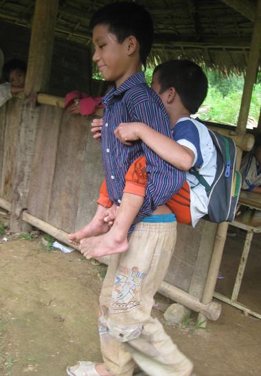 Hàng ngày, Sơn đi bộ suốt chặng đường 4 km bùn lầy đưa em tới trường.