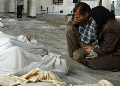 Thân nhân của những người được cho là thiệt mạng trong cuộc tấn công bằng vũ khí hóa học ở ngoại ô Damascus. Ảnh: AFP