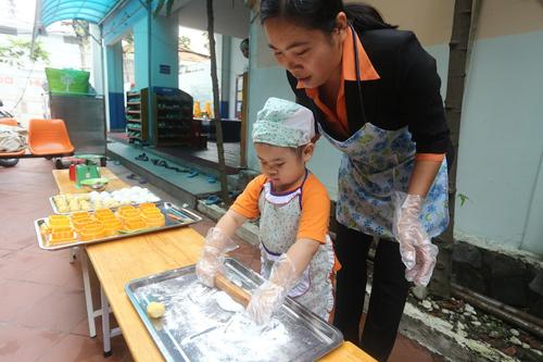 Bé Gia Khanh được cô giáo Ánh cho lên cán bột làm mẫu trước các bạn. Cô bé rất chăm chú khi được giao nhiệm vụ quan trọng.