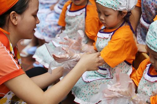 Các bé được các cô cho đi găng tay nhằm tạo các bé ý thức an toàn thực phẩm từ nhỏ
