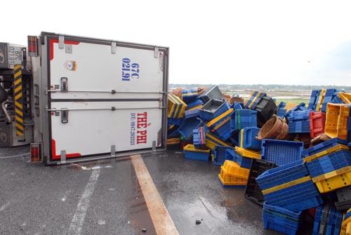 Tai nạn khiến toàn bộ thùng cá trên xe đổ tràn xuống đường. Ảnh: An Nhơn