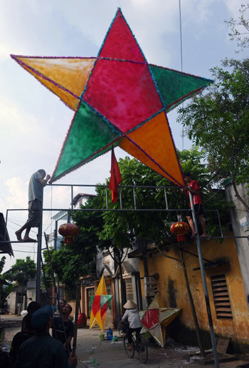 [Caption]ietnamese villagers install a large star-shapped lantern on top of an entrance gate at a village in the outskirts of Hanoi on September 18, 2013 as people prepare to celebrate the traditional Mid-Autumn festival.