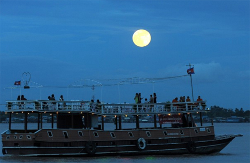 [Caption]The moon rises as a tourist boat sails along the Mekong rRver in Phnom Penh, Cambodia