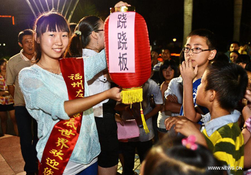 [Caption]People take part in a lantern puzzle contest in Fuzhou, southeast China's Fujian Province, Sept. 19, 2013
