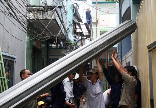 Lực lượng công ích quận 8 có mặt giúp người dân tháo dỡ các căn nhà sập. Ảnh: An Nhơn
