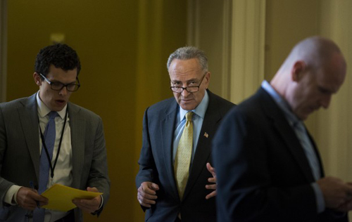 Sen. Charles E. Schumer (D-N.Y.) works with staff outside a closed-door meeting.