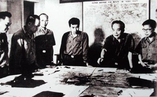 Quân ủy Trung ương đang theo dõi diễn biến Chiến dịch Hồ Chí Minh năm 1975. Trong ảnh, từ trái sang phải: đại tá Lê Hữu Đức (Cục trưởng Cục tác chiến), thượng tướng Hoàng Văn Thái (Phó tổng tham mưu), thiếu tướng Vũ Xuân Chiêm (Phó chủ nhiệm Tổng cục Hậu cần), thượng tướng Song Hào (Chủ nhiệm Tổng cục Chính trị), đại tướng Võ Nguyên Giáp (Tổng tư lệnh, Bộ trưởng Quốc phòng, Bí thư Quận ủy Trung ương), trung tướng Lê Quang Đạo (Phó Chủ nhiệm Tổng cục Chính trị)