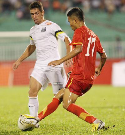 Tiền vệ trẻ trong pha tranh bóng với cầu thủ của Santos. Ảnh: Đức Đồng.
