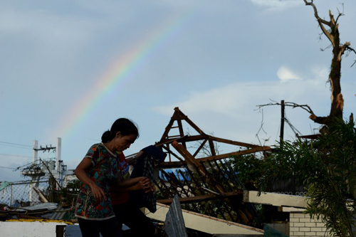 [Caption]Residents walk past debris of destroyed houses in the aftermath of Super Typhoon Haiyan in Tacloban, eastern island of Leyte on November 9, 2013.