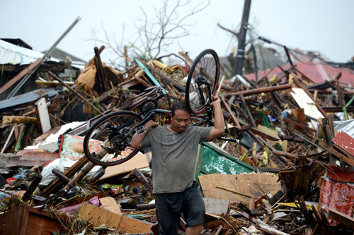 [Caption]A man carries a bike as he walks among debris of destroyed houses in Tacloban, eastern island of Leyte on November 10, 2013