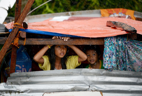 [Caption]Children peek out from their makeshift shelter in Tacloban, on the eastern island of Leyte on November 10, 2013.