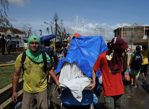 [Caption] Residents push an improvised trolley loaded with an injured relative as they head for a medical station in Tacloban City, Leyte province,central Philippines on November 10, 2013, three days after devastating Typhoon Haiyan hit the city on November 8.