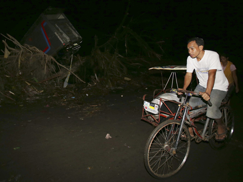 [Caption]Survivor Sandy Torotoro pedals his pedicab along a dark street after powerful Typhoon Haiyan slammed into Tacloban city, Leyte province central Philippines on Saturday, Nov. 9, 2013. The 44 year-old bicycle taxi driver who lives near an airport with his wife and 8 year-old daughter, said he and others took refuge inside a parked Jeep to protect themselves from the storm, but the vehicle was swept away by a surging wall of water.