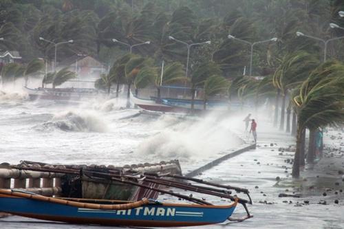 Một người dân đi qua chỗ sóng lớn đập vào bờ ở tỉnh Albay, Philippines, trong bão Haiyan hôm nay. Ảnh: AFP