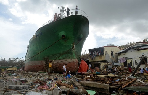 People walk amongst debris next to a ship washed ashore in the aftermath of Super Typhoon Haiyan at Anibong in Tacloban, eastern island of Leyte on November 11, 2013. Hundreds of Philippine soldiers and police poured into a city devastated by Super Typhoon Haiyan on November 11 to try to contain looting that threatens an emergency relief effort.
