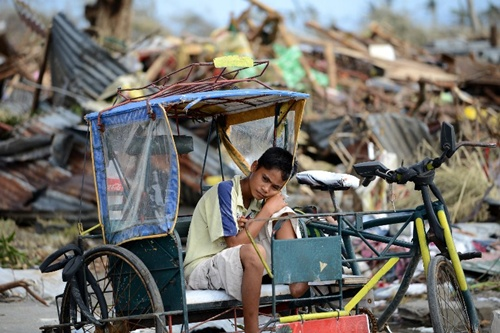 A young survivor rests on a pedicab surrounded by debris caused by Super Typhoon Haiyan in Tacloban in the eastern Philippine island of Leyte on November 11, 2013.