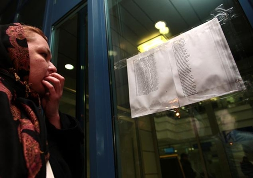 Người phụ nữ đứng đọc danh sách những người có mặt trên chuyến bay gặp nạn. Ảnh: AP.