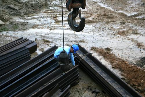 Sau khi đào xong hố, khoanh vùng, dùng cừ sắt để gia cố xung quanh để không cho đất lở. Ảnh: Bá Đô