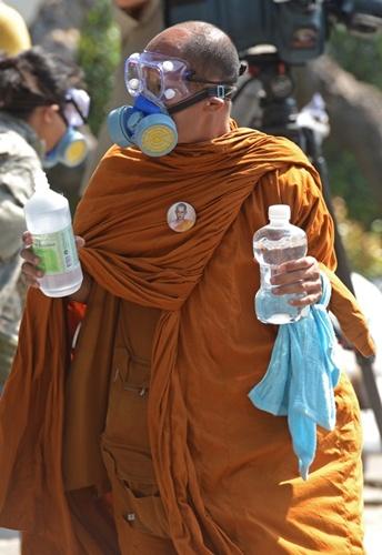 Một nhà sư Thái đeo kính và mặt nạ chống hơi cay chuyên dụng, tay cầm chai nước muối đến với người biểu tình.