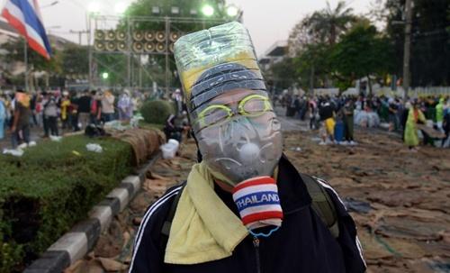 Trong ảnh, một người biểu tình ở Bangkok dùng chai nước, kính bơi