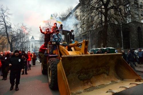 Nhóm người biểu tình quá khích lái xe ủi tấn công cảnh sát chống bạo động trong cuộc biểu tình ở thủ đô Kiev, Ukraine hôm 1/12. Ảnh: AFP.