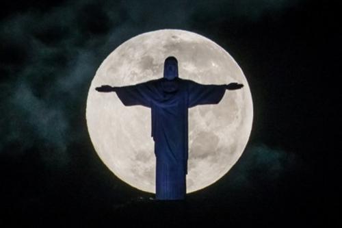 Trăng tròn phía sau Tượng Chúa Cứu Thế ở thành phố Rio de Janeiro, Brazil hôm 25/5. Tượng Chúa cao 38 mét, đứng trên đỉnh núi Corcovado cao 732 mét. Ảnh: AFP.
