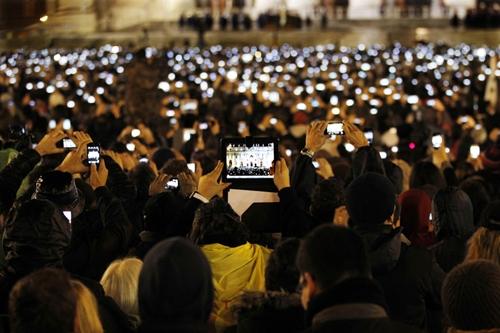 Du khách chụp ảnh giáo 13/3 chụp ảnhHồng y Jorge Bergoglio vẫy tay chào giáo dân từ ban công Vương cung Thánh đườngkhi ông đangphát biểu trênban công Nhà thờ Basilica ở Vatican.Mật nghị Hồng y. Ảnh: AP.