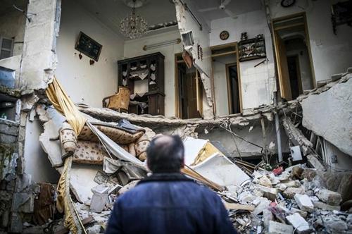 Người dân đứng nhìn căn hộ của mình ở thành phố Aleppo, Syria bị phá hủy do ảnh hưởng từ cuộc nội chiến. Ảnh: AP.